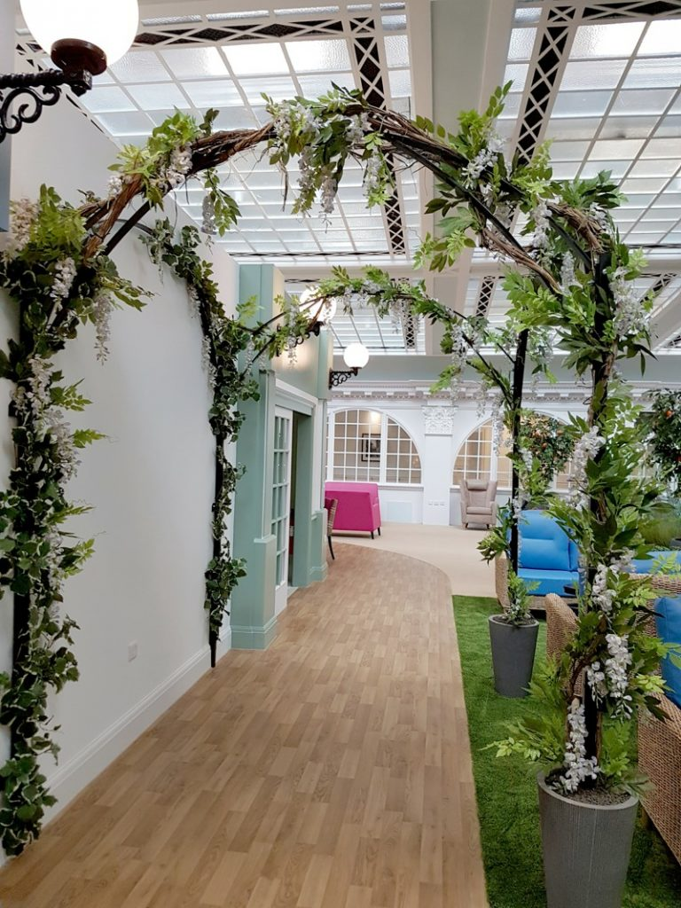 Artificial vines foliated with wisteria applied to bespoke metal pergola