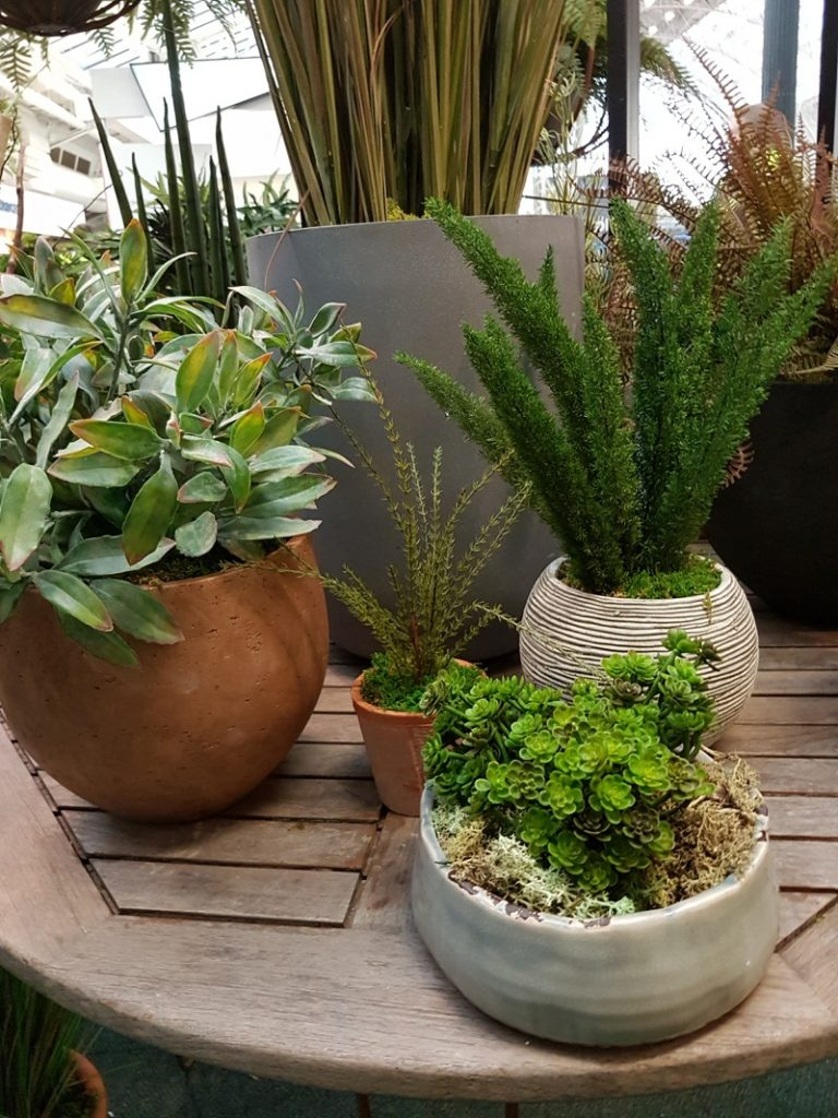 Eclectic mix of artificial plants in pots