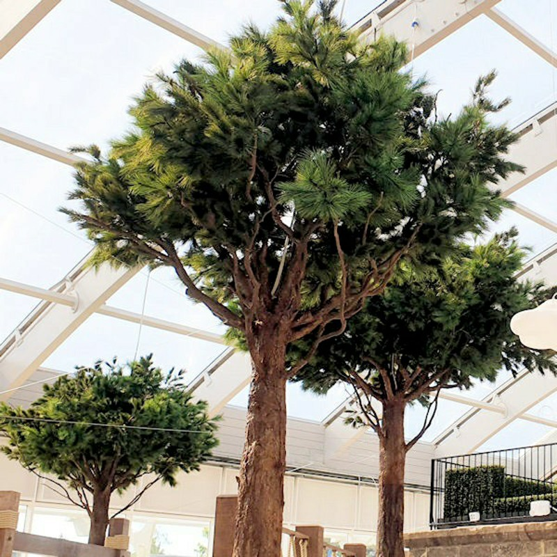 Large Artificial Pine Trees with replica trunks installed in a holiday park