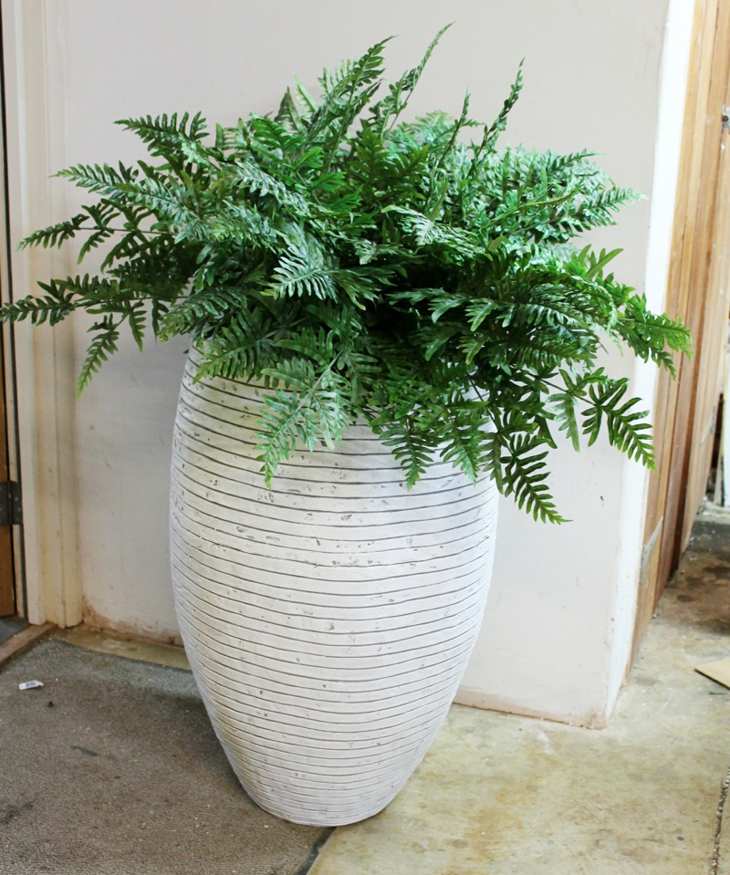 Large artificial fern in white ceramic pot