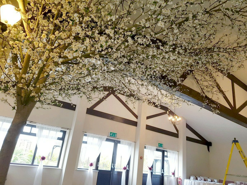 artificial blossom tree with extending canopy over ceiling